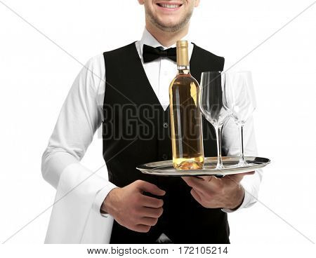 Young handsome waiter holding tray with wine bottle and glasses on white background