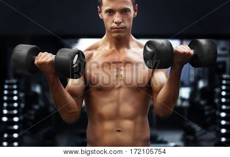 Athletic man training with dumbbells in gym