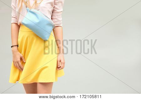 Young woman holding blue leather clutch on light background