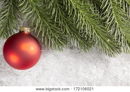 Christmas ball and spruce branch in the snow