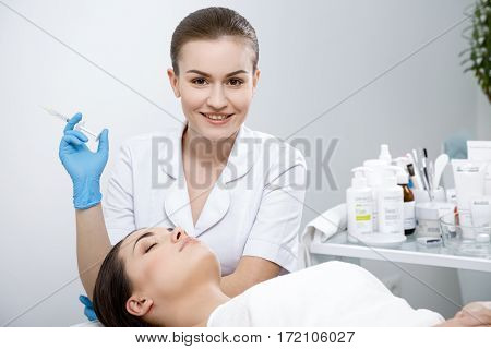 Doctor with syringe with filler for facial contouring or augmentation. Doctor looking at camera. Patient lying on couch with closed eyes. Cosmetological clinic