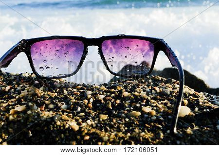 Wet black sunglasses lying on rocks near sea, big wave at background, close up, summertime.