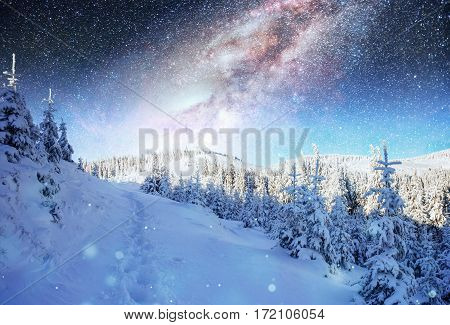 starry sky in winter snowy night. fantastic milky way in the New Year's Eve. The Milky Way is a fantastic New Year's Eve. Winter road in the mountains. Courtesy of NASA.