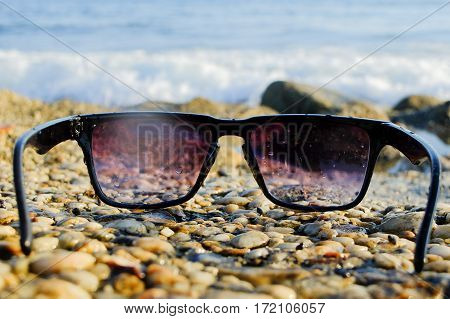 Sunglasses lying on rocks near the sea, copy space, close up, summertime.