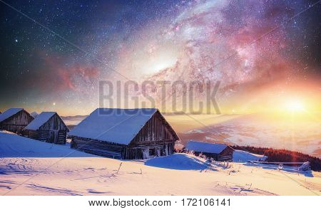 Cabin in the mountains in winter. Mysterious fog. In anticipation of holidays. Fantastic starry sky and the milky way.  Courtesy of NASA. Carpathians. Ukraine, Europe