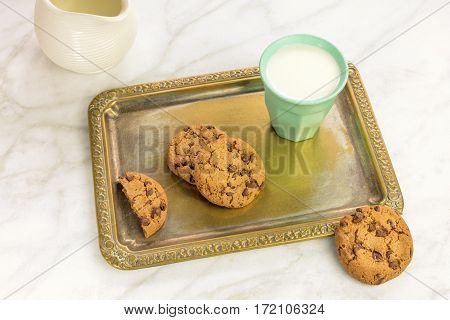 A photo of chocolate chips cookies on a vintage tray with a glass of milk and a milk jar, with a place for text