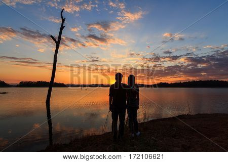 Shadow of couple standing at the lake in sunset time