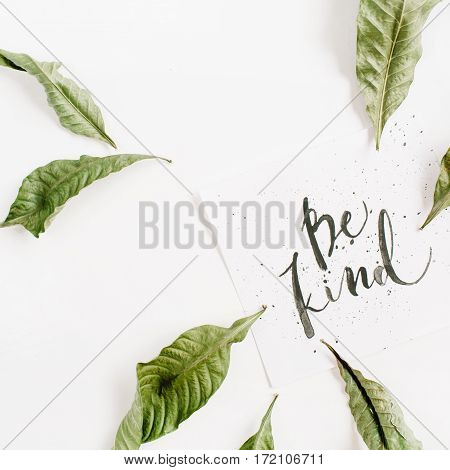 Minimalistic composition with words Be Kind written in calligraphic style on paper with leaf frame on white background. Flat lay top view