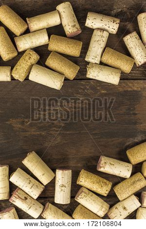 Many wine corks forming a frame on a dark wooden background texture with a place for text. A vertical design template for a tasting invitation or restaurant menu