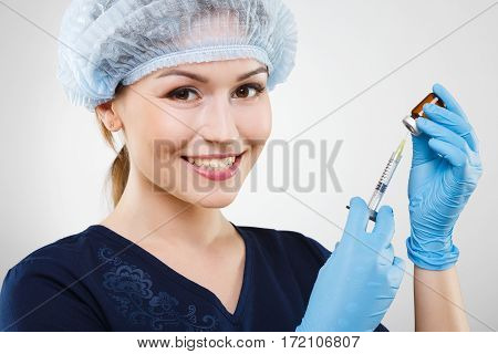 Smiling  nurse with nude make up wearing blue medical uniform, medical hat and gloves at gray background, holding syringe.