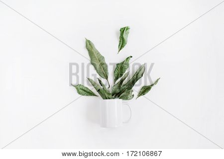 Blank template of white mug and green leaves bouquet on white background. Flat lay top view.