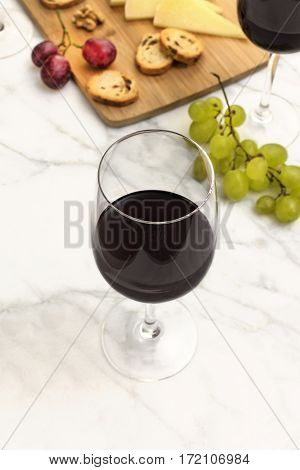 A photo of a wine and cheese tasting, with bread, grapes, glasses of red wine, a cork and a place for text