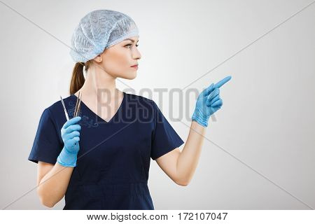 Beautiful nurse with brown hair and nude make up wearing blue medical uniform and gloves at gray background and holding a scalpel.
