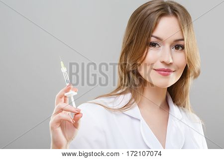 Portrait of nurse with brown hair and nude make up wearing white medical robe at gray background and posing with syringe.