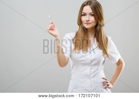 Attractive nurse with brown hair and nude make up wearing white medical robe at gray background and posing with syringe.