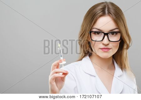 Nurse with brown hair and nude make up wearing white medical robe, glasses at gray background and posing with syringe, portrait.