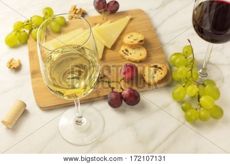A photo of a wine and cheese tasting, with bread, grapes, glasses of white and red wine, a cork and a place for text