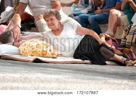 OSTROG MONASTERY, MONTENEGRO - JULY 25, 2016: woman pilgrim elderly resting lying down awaiting the Holy Mass
