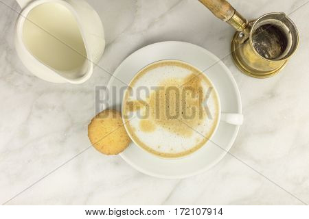 A photo of a cup of coffee with milk with a butter cookie, milk jug, and an emptied Turkish coffee pot, shot from above on a light texture for copy space