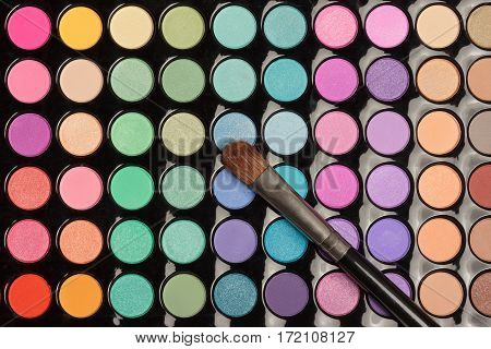 Colorful eyeshadow palette with makeup brush. View from above. Flat lay