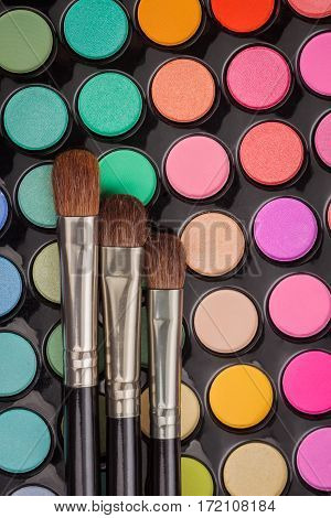 Make-up brushes on colorful eyeshadow make-up palette. Flat lay. Top view