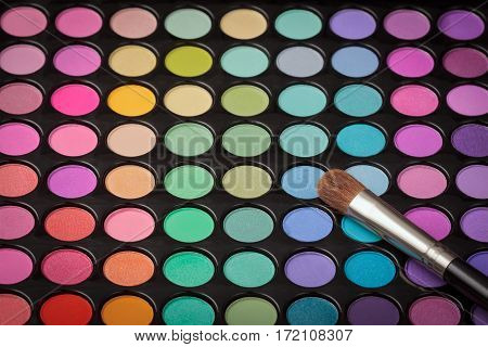 Makeup brush on colorful eyeshadow makeup palette with copyspace