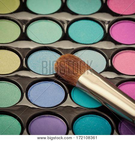 Closeup of makeup brush on makeup eyeshadow palette. Macro makeup brush