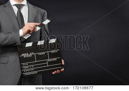 Man holding movie clapper board on chalkboard background with copyspace