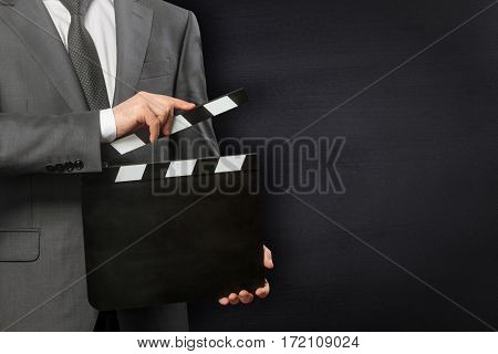 Man holding blank movie clapper board on black background