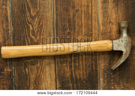 Used and rusty hammer on a wooden background