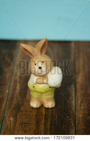 Ceramic painted rabbits for Easter decoration on a wooden background
