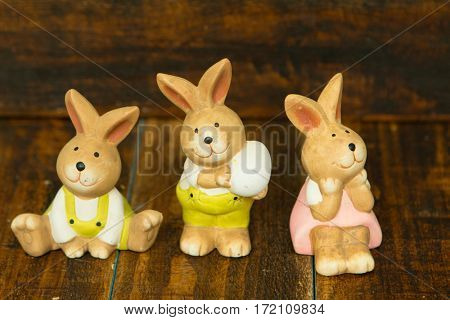 Three ceramic painted rabbits for Easter decoration on a wooden background