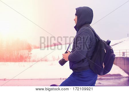 Young photographer smitrit forward on the banks of the dam. A traveler on the background of winter landscape. It surrounds winter nature.
