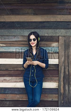happy asian woman listening to music on her headphone and holding smartphone leaning against old wooden barn wall vintage retro color style