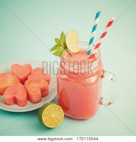 Close-up of watermelon smoothie in Mason jar decorated with lime, mint, straws. Watermelon slices curved like hearts on plate
