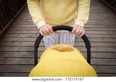 Young woman strolling a carriage outdoor. Closeup shot of female hands with stroller handle