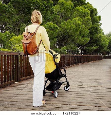 Young mother walking with newborn in stroller in green park