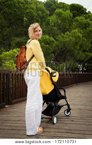 Joyful young mother strolling with newborn in carriage. Woman walking in park with stroller. Green trees on background