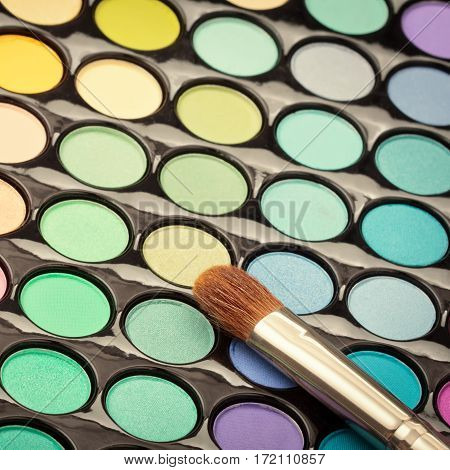 Close-up of eyeshadow palette with makeup brush