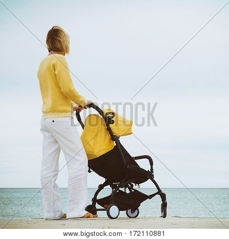 Young mother ooking through the sea while holding stroller outdoor