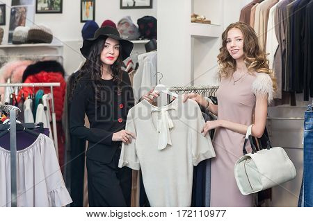Two young woman, friends, sisters are shopping at store. Women shopping choosing dress. Beautiful young shoppers in clothing store.