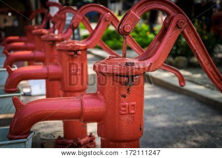 Red hand water pumps in front focus.