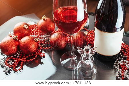 Christmas and New Year. Festive decorations, bottle of red wine and glass on the dark background.