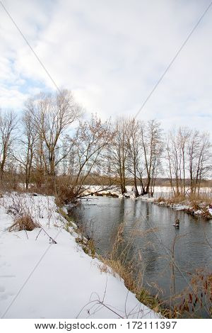 The quiet river flows in the winter between snow-covered coast