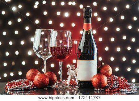 Christmas and New Year. Festive decorations, bottle of red wine and two glasses on the background lights.