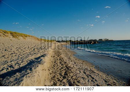 A sandy beach with tons of shells and crystal blue water - Horizontal
