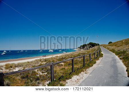 An island with beautiful beach and crystal clear water with a road