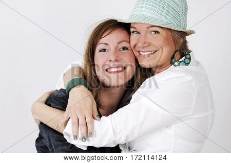 Two trendy hipster woman hugging each other and having fun together. Isolated on white background.