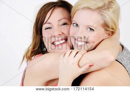 Portrait of two young women hugging each other. Isolated with light background.