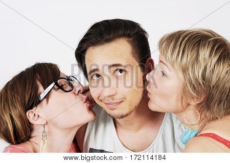 Two funny hipster women are kissing a guy on the cheek from two sides. Isolated with white background.